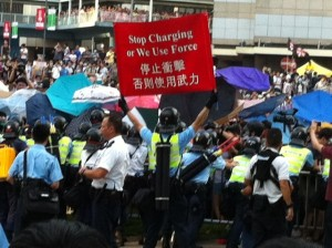 The police held up a warning banner to stop people from joining those already at the Government Headquarters protest site
